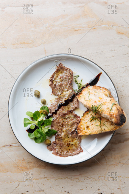 Top view of tasty fried pieces of meat on white plate with roasted bread decorated with sauce greenery and metal fork in restaurant