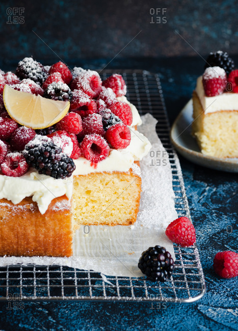 Sliced lemon pound cake with cream and fresh berries on a wire rack, blue background
