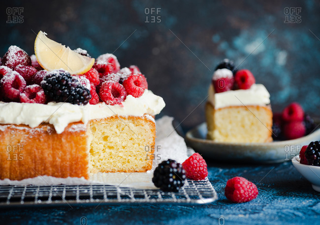 Sliced lemon pound cake with cream and fresh berries on a wire rack on a blue background