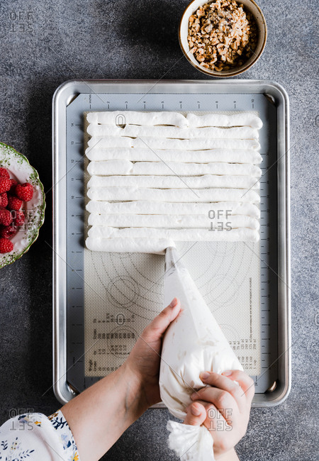 Woman piping meringue on baking tray while making a meringue roll with nuts and berries