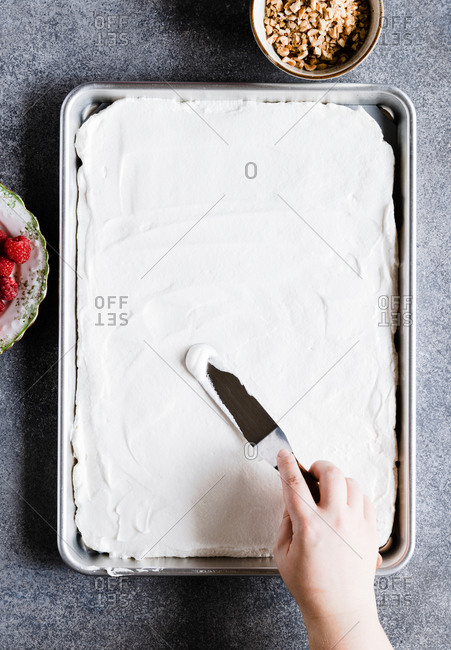 Woman spreading meringue on baking tray while making meringue roll from above