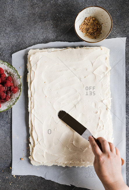 Overhead view of woman spreading meringue on baking tray while making meringue roll
