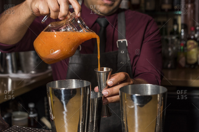 Bartender pouring juice for a cocktail