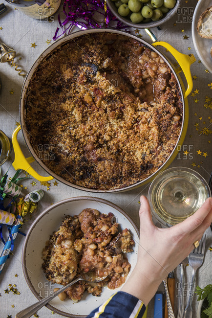 Festive New Year's Eve table with pot of cassoulet and champagne