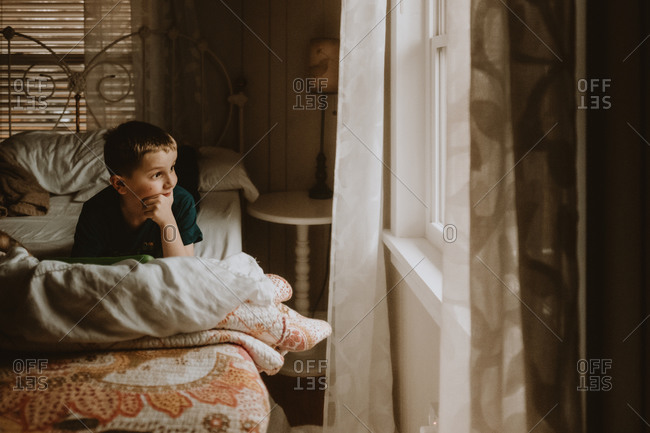 Young boy staring out bedroom window