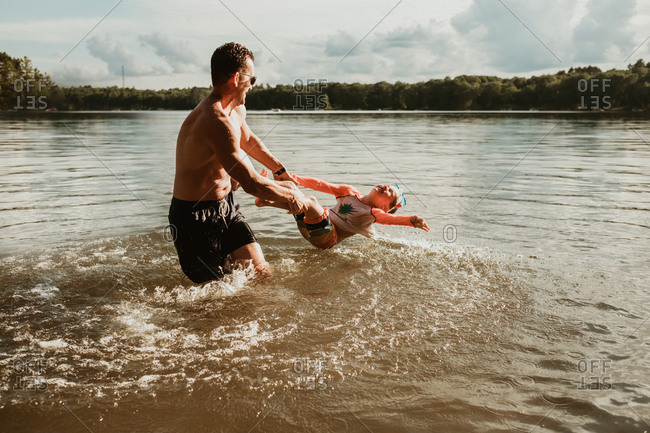 Father spinning his son on top of the water during the summer in a lake in northern Wisconsin