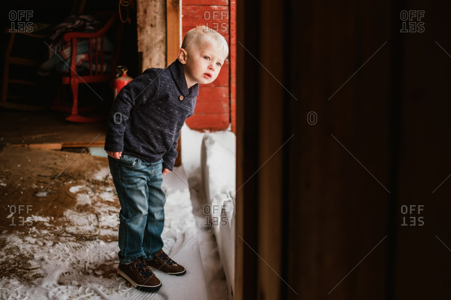 Toddler boy standing inside a barn looking out at the snow outside