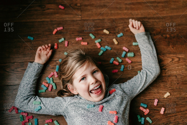 Overhead view of a little girl laying in candy
