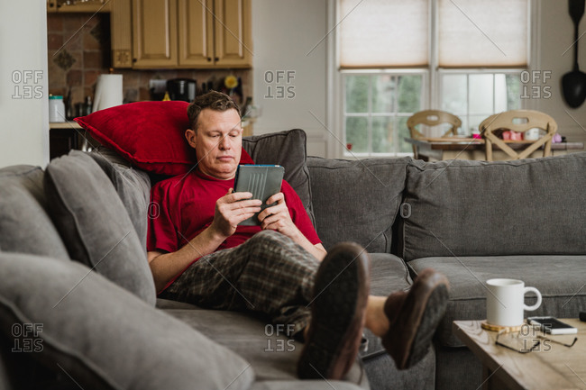 Man reading on a tablet while relaxing on sofa