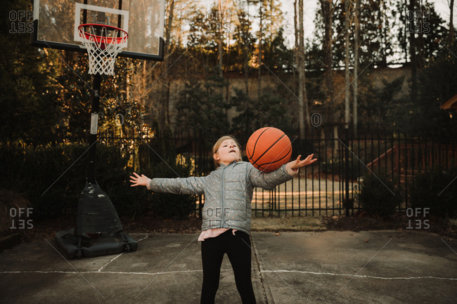 Girl playing basketball in her driveway