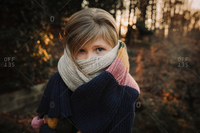 Portrait of a girl with a scarf wrapped around her face and neck