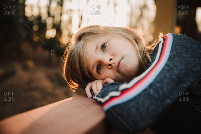Portrait of a serious girl resting her head outdoors