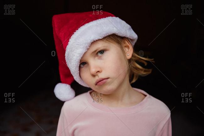 Serious girl wearing a Santa hat