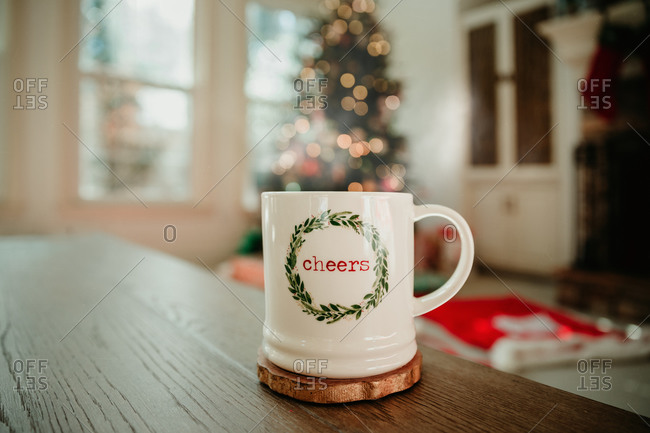A Christmas mug with cheers and a wreath
