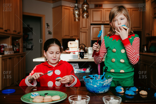 Girls in the their Christmas pajamas decorating cookies