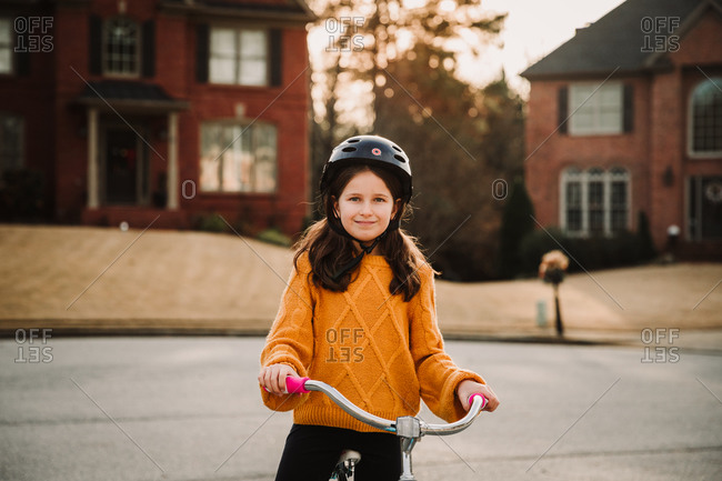 Girl in a yellow sweater riding a bike