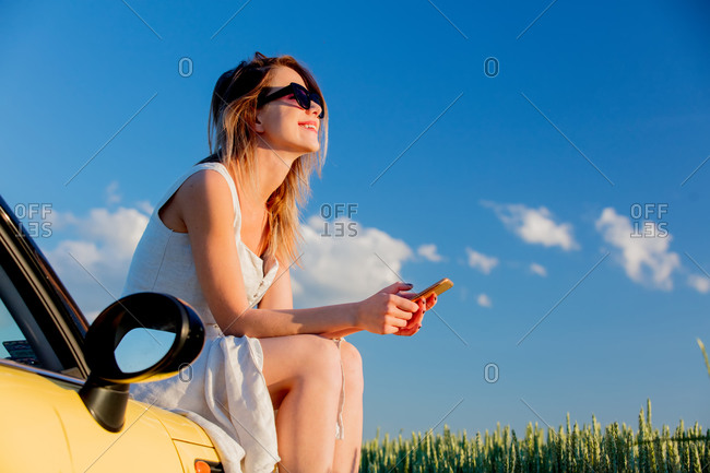 Young girl in sunglasses with smartphone is sitting on a car on green wheat field in spring time
