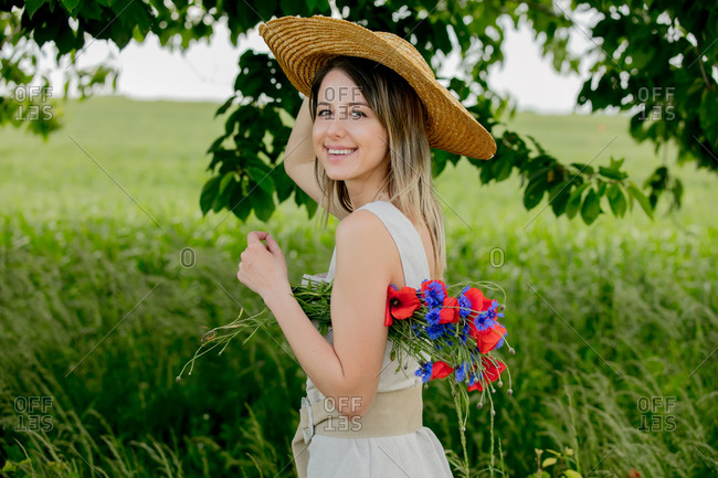 Young woman in dress and with hat stay near field with bouquet of centaurea and poppy flowers