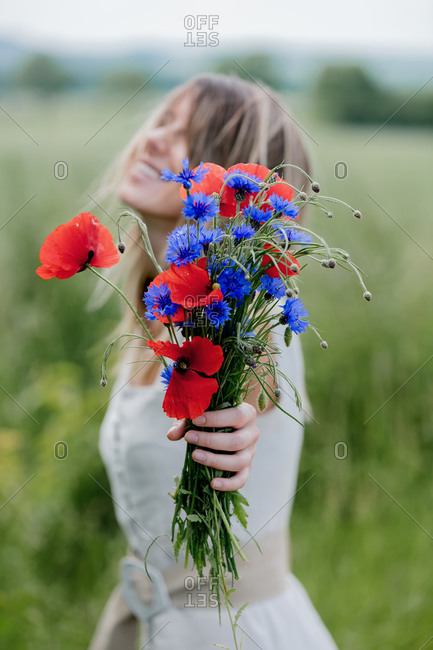 Young woman in dress stay near field with bouquet of centaurea and poppy flowers