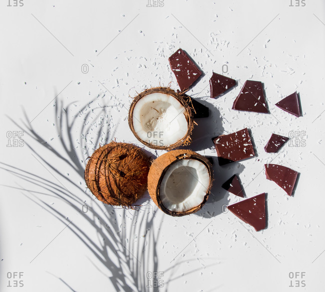 Coconuts and dark chocolate on white background with shadows