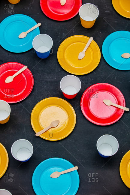 Colored plates and glasses on the table are ready for the party