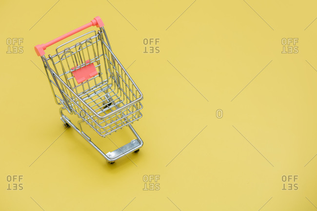 Little shopping cart on yellow background