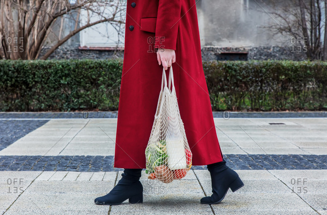 Style woman in red coat and net bag waking home after shopping.