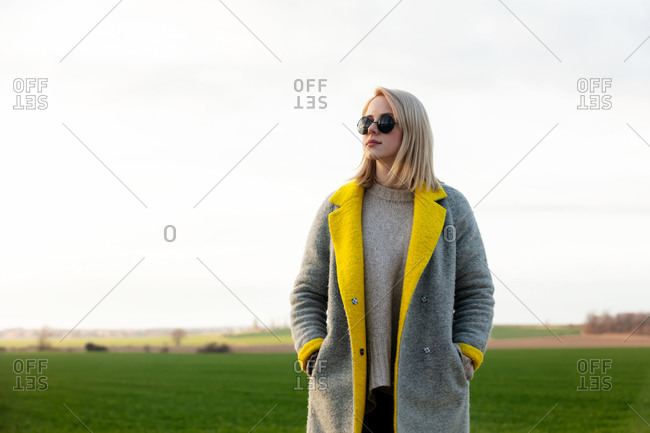 Style woman in sunglasses and coat at countryside
