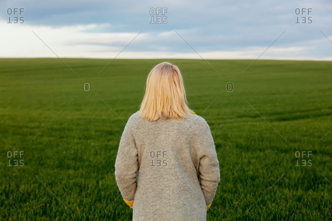 Style blonde in coat in green wheat field