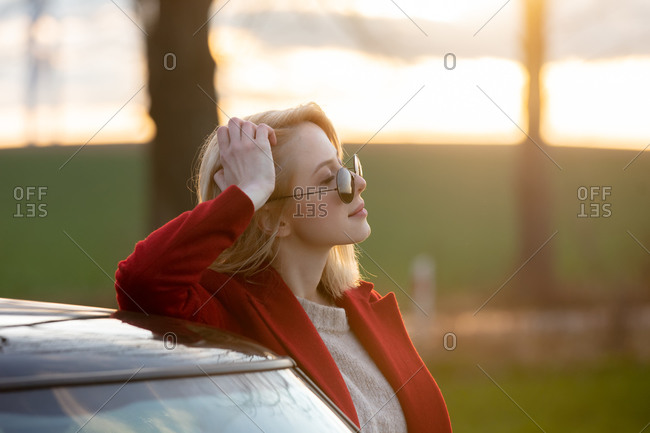 Style blonde woman in sunglasses and red coat near car at countryside