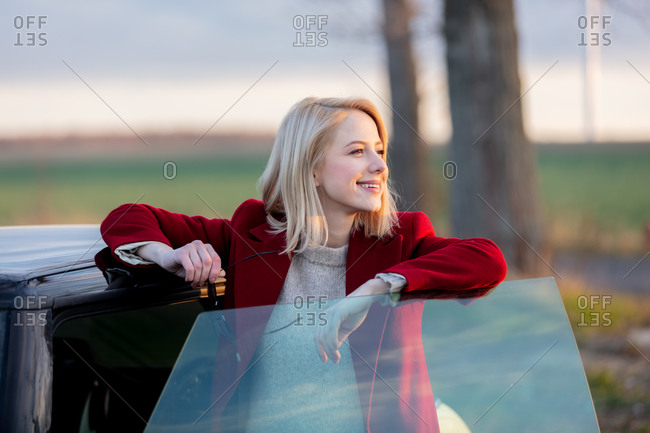 Style blonde woman in red coat at countryside