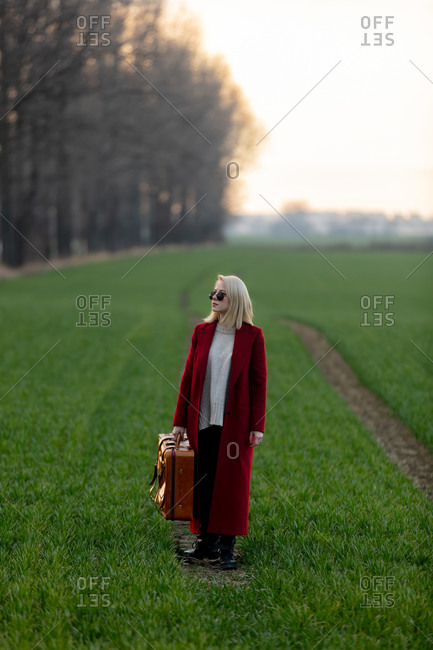 Style blonde woman with suitcase at countryside