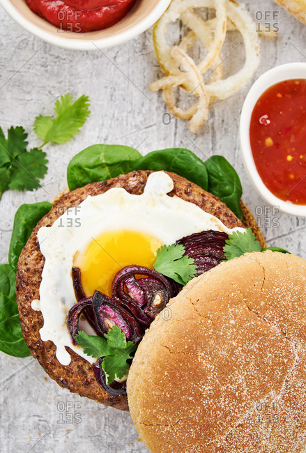 Overhead view of a hamburger with egg on gray background