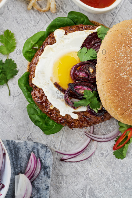 Top view of a hamburger with egg on gray background