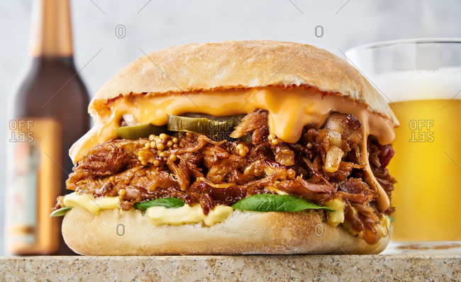 A pulled pork sandwich served with beer