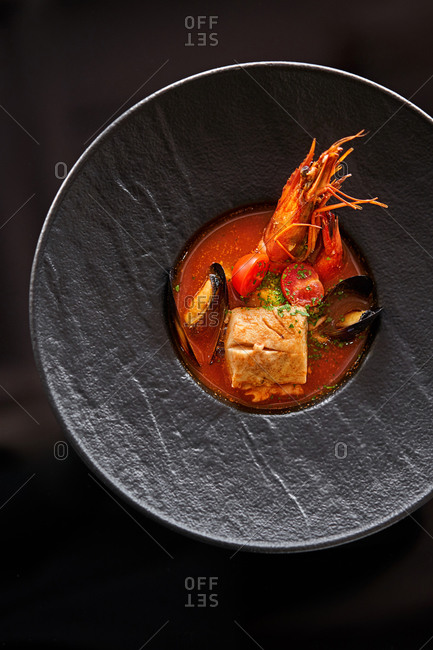 Seafood soup in a black bowl on dark background