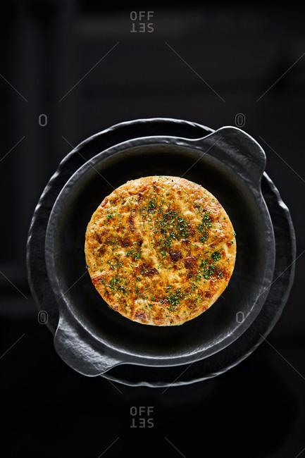 Egg frittata in a black bowl on dark background