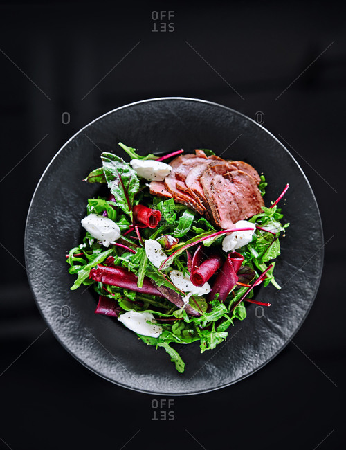 Salad with beets and meat in a black bowl