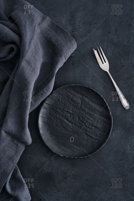 Black plate on dark surface with linen napkin and fork