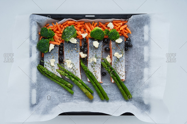 Raw fish in a baking dish with fresh vegetables