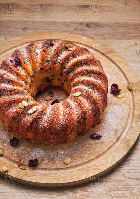 Bundt cake with cranberries and pumpkin seeds on a wooden board