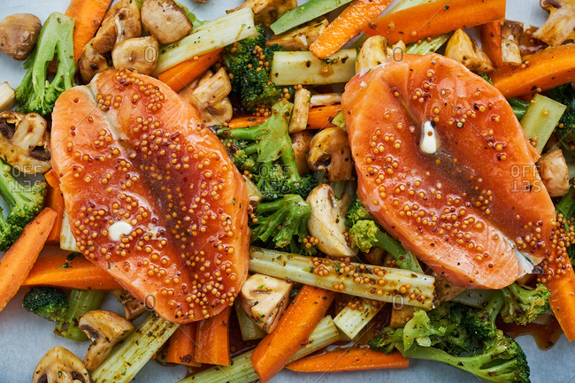 Two raw fish fillets with fresh vegetables and sauce