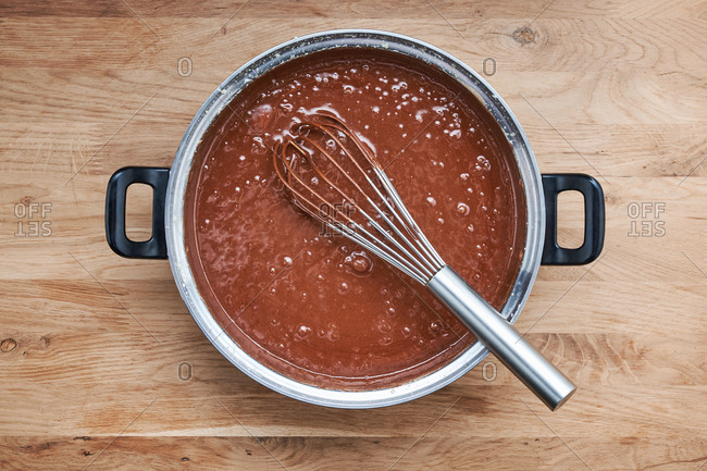 Chocolate batter in a pot with whisk