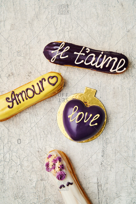 Love-themed eclairs and heart cake on light surface