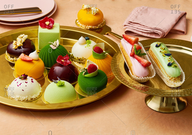 Colorful gourmet desserts and eclairs on gold trays