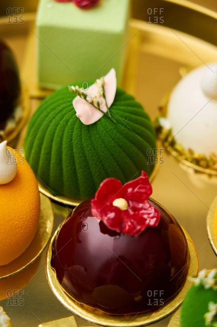 Colorful gourmet miniature cakes on a gold tray