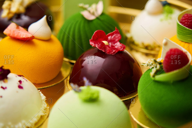 Close up of colorful gourmet miniature cakes on a gold tray