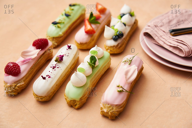 Variety of gourmet eclairs topped with fruit