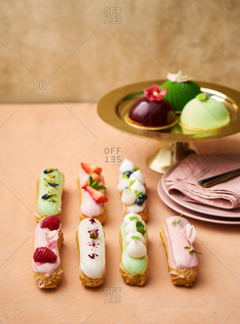 Eclairs topped with fruit beside a gold tray with mini cakes