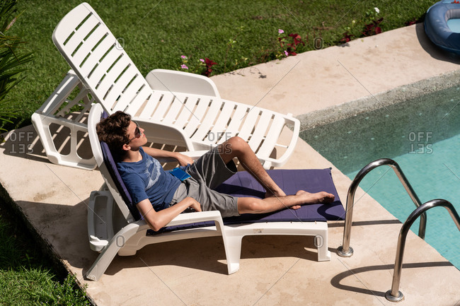Teenage boy relaxing on poolside lounge chair